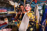 "19 AUGUST 2014 - BANGKOK, THAILAND:  Members of the Lehigh Leng Kaitoung Opera troupe put on their costumes before a performance at the Chaomae Thapthim Shrine, a small Chinese shrine in a working class neighborhood of Bangkok. The performance was for Ghost Month. Chinese opera was once very popular in Thailand, where it is called ""Ngiew."" It is usually performed in the Teochew language. Millions of Chinese emigrated to Thailand (then Siam) in the 18th and 19th centuries and brought their culture with them. Recently the popularity of ngiew has faded as people turn to performances of opera on DVD or movies. There are still as many 30 Chinese opera troupes left in Bangkok and its environs. They are especially busy during Chinese New Year and Chinese holiday when they travel from Chinese temple to Chinese temple performing on stages they put up in streets near the temple, sometimes sleeping on hammocks they sling under their stage. Most of the Chinese operas from Bangkok travel to Malaysia for Ghost Month, leaving just a few to perform in Bangkok.        PHOTO BY JACK KURTZ"