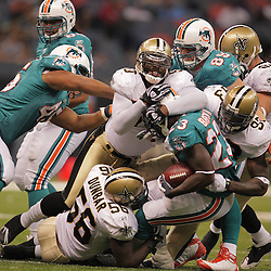 2008 August 28: New Orleans Saints defenders Marvin Mitchell (50), Bobby McCray (93) and Jo-Lonn Dunbar (56) gang tackle Miami Dolphins running back Ronnie Brown (23) during their game at the Louisiana Superdome in New Orleans, LA.