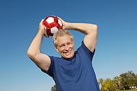 Senior man holding soccer ball over head, outdoors