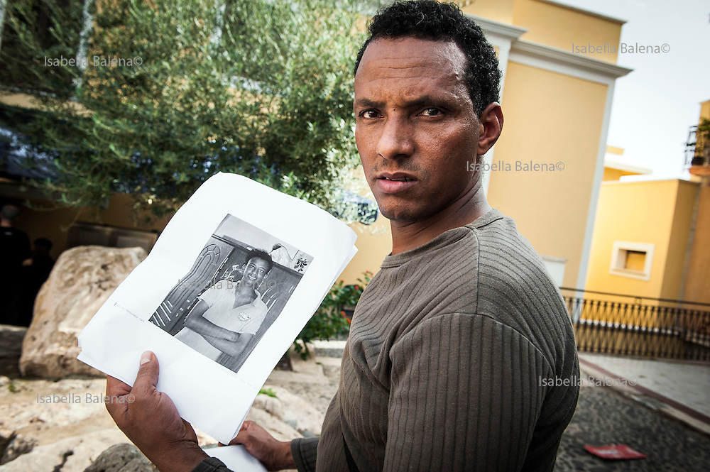 Lampedusa, Sicilia, Italy, ott 2013. Medhani Mulue con la foto del cugino scomparso nel naufragio del 3 ottobre 2013. Pictures of disappeared migrants the night of 3 oct 2013