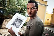 Lampedusa, Sicilia, Italy, ott 2013. Medhani Mulue con la foto del cugino scomparso nel naufragio del 3 ottobre 2013. Pictures of disappeared migrants the night of 3 oct 2013