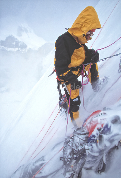 American mountaineer Jay Smith belaying in spindrift avalanches during a 1996 attempt to climb the north face of Thelay Sagar in the Garwal Himal of India.