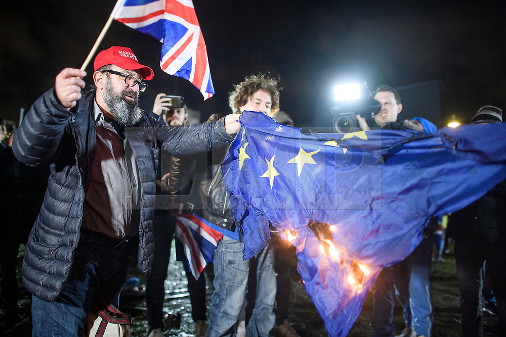 © Licensed to London News Pictures. 31/01/2020. London, UK. Brexit supporters burn the EU flag shortly after 11pm, outside Parliament in Westminster, London, as the UK leaves the European Union. 51. 9% of the UK population voted to leave the EU in a referendum in June 2016. Photo credit: Ben Cawthra/LNP