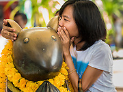 20 SEPTEMBER 2015 - SARIKA, NAKHON NAYOK, THAILAND: A woman whispers a prayer to the mouse who is Ganesha's assistant at the Ganesh festival at Shri Utthayan Ganesha Temple in Sarika, Nakhon Nayok. Ganesh Chaturthi, also known as Vinayaka Chaturthi, is a Hindu festival dedicated to Lord Ganesh. Ganesh is the patron of arts and sciences, the deity of intellect and wisdom -- identified by his elephant head. The holiday is celebrated for 10 days. Wat Utthaya Ganesh in Nakhon Nayok province, is a Buddhist temple that venerates Ganesh, who is popular with Thai Buddhists. The temple draws both Buddhists and Hindus and celebrates the Ganesh holiday a week ahead of most other places.    PHOTO BY JACK KURTZ