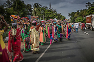 Women walk in a procession along the East Coast Road (ECR) to prepare a meal on the grounds of Iyyanarappan Temple as part of the Ganesh Chaturthi Festival. Chinna Mudaliyar Chavady, Tamil Nadu, India.