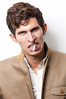 Portrait of angry young man smoking over white background