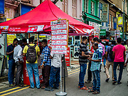 "09 JULY 2017 - SINGAPORE: A tent set up by Singtel, a Singapore cellular carrier, on a street in Little India in Singapore. Guest workers from the Indian sub-continent buy Singapore SIM cards at the tent. There are hundreds of thousands of guest workers from the Indian sub-continent in Singapore. Most work 5 ½ to six days per week. On Sundays, the normal day off, they come into Singapore's ""Little India"" neighborhood to eat, drink, send money home, go to doctors and dentists and socialize. Most of the workers live in dormitory style housing far from central Singapore and Sunday is the only day they have away from their job sites. Most work in blue collar fields, like construction or as laborers.    PHOTO BY JACK KURTZ"