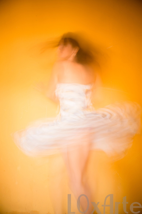 Carefree young woman in white pattern dress dancing in front of a hot yellow background.