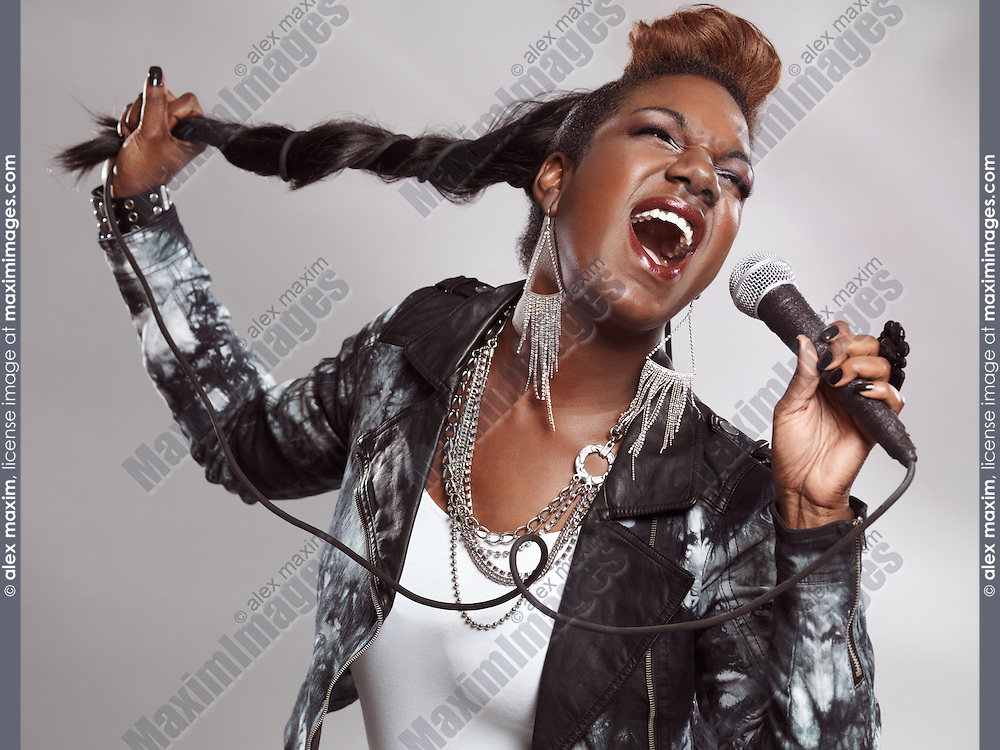Artistic photo of a black woman singing in microphone with cord wrapped around her hair