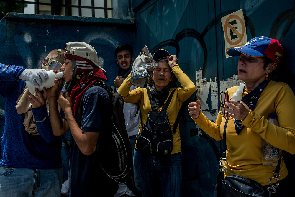 CARACAS, VENEZUELA - APRIL 19, 2017:  Protesters recover after being badly tear gassed by authorities.  Thousands of protesters took to the streets today in Venezuela to show their discontent with the government.  They were met by riot police that fired tear gas and rubber bullets at them.  Some protesters responded by throwing rocks and petrol bombs.  Venezuela is in crisis, and residents face daily struggles over food and medicine shortages, and one of the highest crime rates in the world.  PHOTO: Meridith Kohut