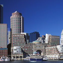 .Boston Harbor Skyline, day. Rowes Wharf,  Boston Harbor Hotel (center with arch). Customs house tower (right). Financial district high-rise buildings (rear) . Massachusetts.