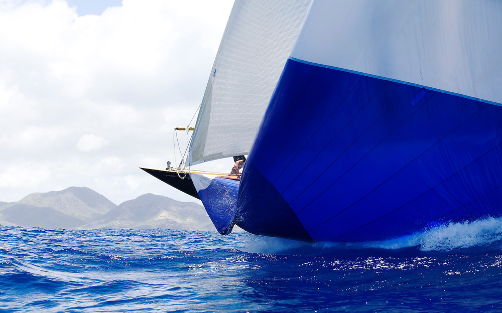 A bow man hidden behind the huge sail of a the J Class yacht Valsheda during Antigua Classic Yacht Regatta. This yacht race is one of the worlds most prestigious traditional yacht races. It is held annually off the coast of Antigua.