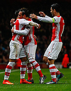 Alexis Sanchez of Arsenal (left) celebrates scoring his team's second goal against R.S.C Anderlecht with Santi Cazorla (centre) and Mikel Arteta (right) during the UEFA Champions League match at the Emirates Stadium, London<br /> Picture by David Horn/Focus Images Ltd +44 7545 970036<br /> 04/11/2014