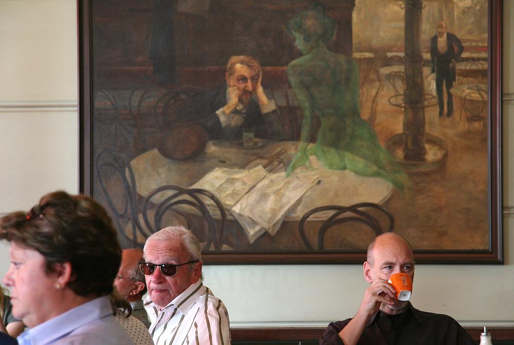 G&auml;ste im ber&uuml;hmten Kaffeehaus SLAVIA in der Prager Innenstadt. Im Hintergrund das Gem&auml;lde &quot;Der Absinthtrinker&quot; von Maler Viktor Oliva.<br /> <br /> Visitors at the famous Caf&eacute; Slavia in the city centre of Prague. In the back a painting by Viktor Oliva with the title the Absinth drinker.