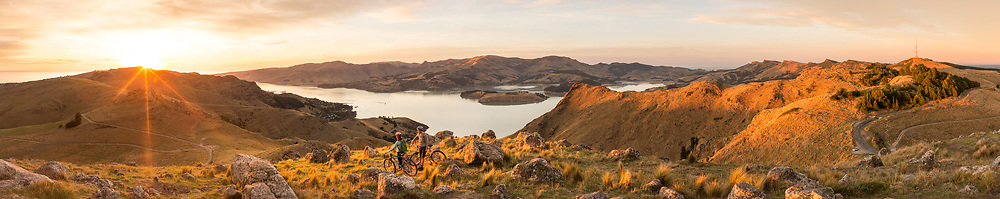 Two mountainbikers watching the sunrise over Lyttleton harbour