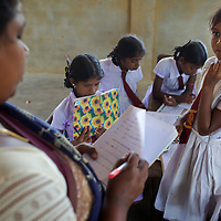 Staff and pupils in class at the Thikilivattai Government Tamil Mixed School in Batticaloa District.<br /> <br /> Thikilivattai Government Tamil Mixed School reopened in May 2008 after local conflict between the LTTE and SLA  troops eased. There are now 351 students in grades 1-9 with a teaching staff of 18. The school has no water supply. Though many of the pupils' parents are not well educated themselves (most are employed in casual paddy cultivation, fishing and seasonal day-wage labour), there is a parents' mobilisation committee that encourages pupil attendance and is involved in helping keep the school clean. The school has an active sports department. Many of the students suffer with the trauma and stress associated with those living in conflict situations. The staff must deal with these issues as well as the personal difficulties that they themselves suffer living in a conflict environment. UNICEF have provided three temporary learning spaces to make up for the lack of space in the original school building. A further two classes must be accommodated beneath trees. UNICEF have also supplied the school furniture.<br /> <br /> Photo: Tom Pietrasik<br /> Batticaloa District, Sri Lanka<br /> September 30th 2009