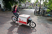 In Utrecht rijdt een vrouw al bellend op een bakfiets die te huur is bij een fietsenstalling van de gemeente.<br /> <br /> In Utrecht a woman is riding a cargo bike while on the phone.