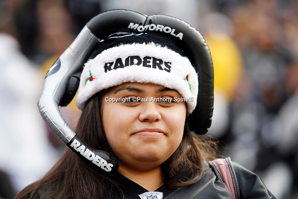 A fan wears a Christmas hat and fake headset as the Oakland Raiders take the field during the NFL week 16 football game against the Indianapolis Colts on Sunday, December 26, 2010 in Oakland, California. The Colts won the game 31-26. (©Paul Anthony Spinelli)