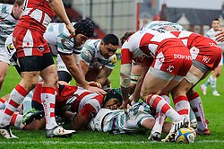 London Irish Lock (#4) George Skivington sneaks through a tackle from Gloucester Flanker (#7) Akapusi Qera to score a try with an outstretched arm during the first half of the match - Photo mandatory by-line: Rogan Thomson/JMP - Tel: Mobile: 07966 386802 05/01/2013 - SPORT - RUGBY - Kingsholm Stadium - Gloucester. Gloucester Rugby v London Irish - Aviva Premiership.