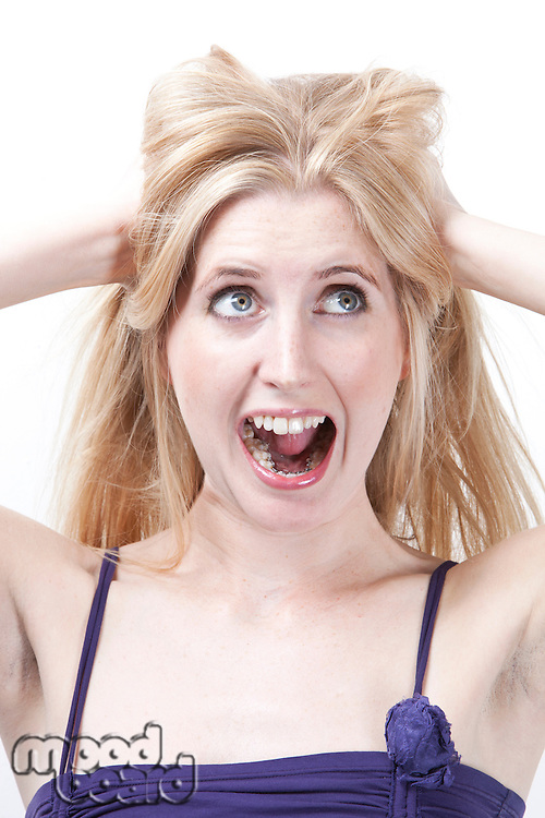 Angry young woman with hands in hair screaming against white background