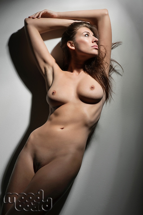 Front view of beautiful young woman posing naked over colored background