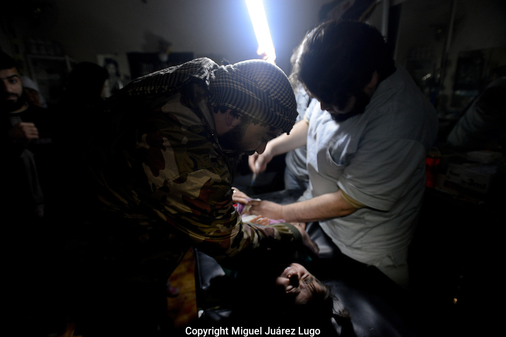Aleppo, Syria, December, 2012,- Working in almost total darkness and without anesthesia or painkillers, nurses try to extract pieces of shrapnel from a little girl's abdomen in the clinic of Dr. Mohamed Hut. The situation is typical in this city, which has been without electricity for more than a month.(Photo by Miguel Juárez Lugo)