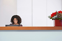 Receptionist sitting behind reception desk Using computer