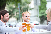 Happy businesspeople toasting beer glasses at outdoor restaurant