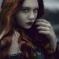 Close up dark portrait of a girl with red hair looking at camera