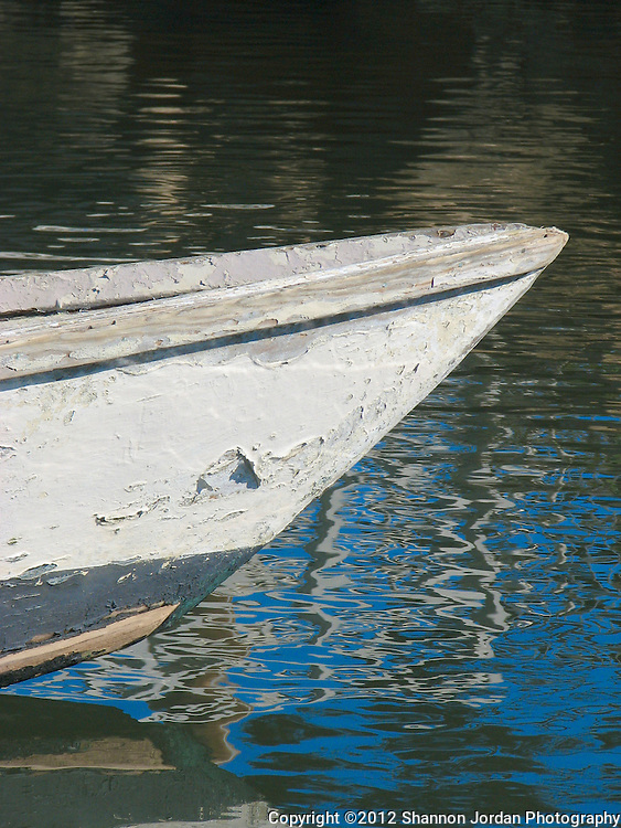 an old canoe rests int he waters of Morro Bay with the reflection of the stacks from the power plant near by.