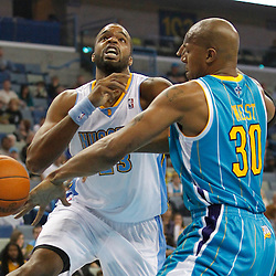 October 29, 2010; New Orleans, LA, USA; Denver Nuggets power forward Shelden Williams (23) has the ball knocked away by New Orleans Hornets power forward David West (30) during the first half at the New Orleans Arena.  Mandatory Credit: Derick E. Hingle..