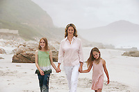 Mother with two daughters (7-9 10-12) walking on beach