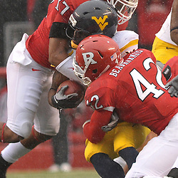 Dec 5, 2009; Piscataway, NJ, USA; Rutgers linebacker Steve Beauharnais (42) and linebacker Damaso Munoz (17) tackle West Virginia running back Noel Devine (7) during first half NCAA Big East college football action between Rutgers and West Virginia at Rutgers Stadium.