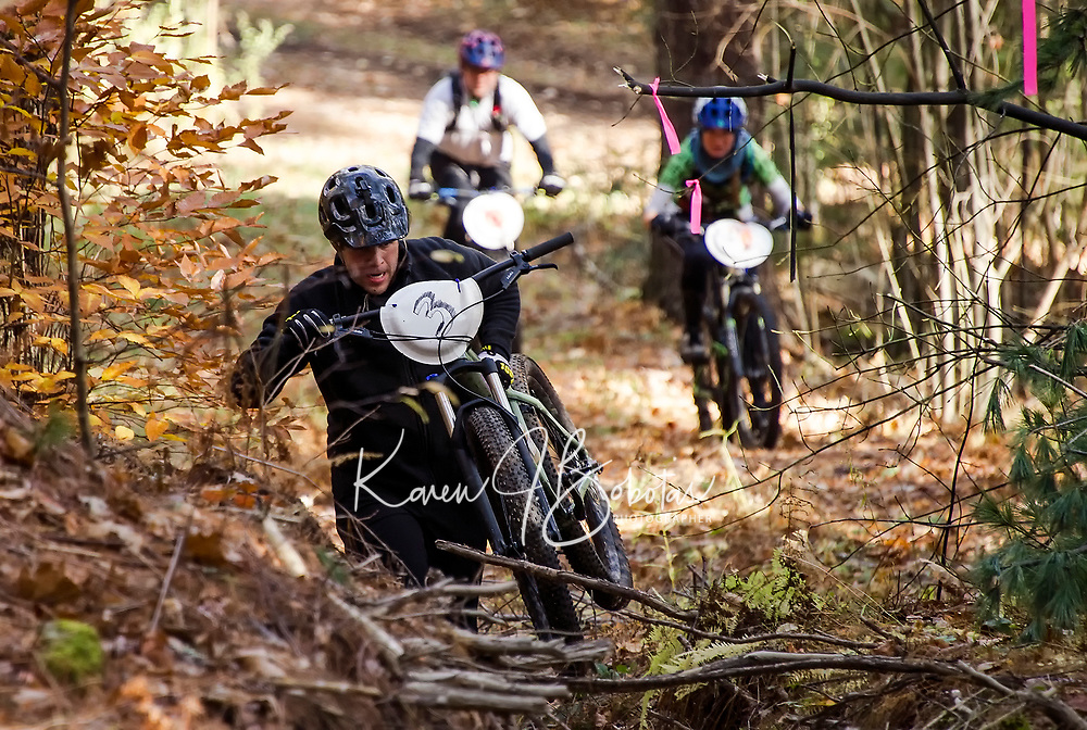Evan Noce carries his bike over obstacles as he heads up Cobble Crown trail during Gunstock's Fall Flurry mountain bike race on Saturday morning.  (Karen Bobotas/for the Laconia Daily Sun)