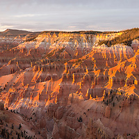 Beautiful golden light at sunset brightly illuminates the canyon walls of Cedar Breaks National Monument, Utah.