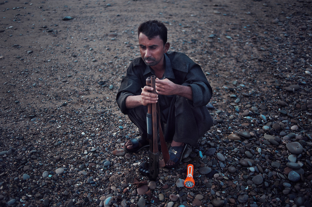 Security guardSher Ali, 31years old cleans his shotgun of rust with a rock off the beachat the Gaddani Ship Breaking Yard, Balochistan Province, Pakistan on August 16, 2011. He is from Balochistan and has three children. He lives on the plot when working..