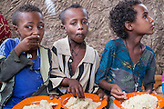 Taymen, Ethiopia - 17.05.16  - Desmil Mulluye, 8, Adnew Abebaw, 9, and Metadel Tifto, 9, eat a lunch of porridge at a CBM-supported school feeding program at Taymen primary school in the district of East Belessa, Ethiopia on May 17, 2016.  Desmil and Adnew are physically impaired, and Metadel is deaf. They do not receive special classes, and are incorporated in normal classroom routines. Photo by Daniel Hayduk
