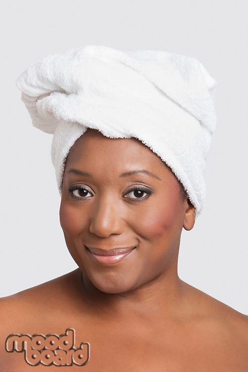 Portrait of mixed race woman with towel wrapped on head over white background