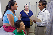 20 JUNE 2009 - PHOENIX, AZ: Mireya Renteria (CENTER BLUE BLOUSE) translates for Dr. Naved Khan (RIGHT) while he talks to Maria Reza (LEFT) and her son in an exam room at the Cultural Cup. The walk in clinic at the Cultural Cup Food Bank started two years ago when Cultural Cup founder Zarinah Awad wanted to expand the food bank's outreach and provide basic medical care for the people who use the food bank. The clinic sees, on average, 7 - 11 patients a week. Awad said that as the economy has worsened since the clinic opened and demand has steadily increased. She attributes the growth to people losing their jobs and health insurance. The clinic is staffed by volunteers both in the office and medical staff. Adults are seen every Saturday. Children are seen one Saturday a month, when a pediatrician comes in. Awad, a Moslem, said the food bank and clinic are rooted in the Moslem tradition of Zakat or Alms Giving, the giving of a small percentage of one's income to charity which is one of the Five Pillars of Islam.   PHOTO BY JACK KURTZ