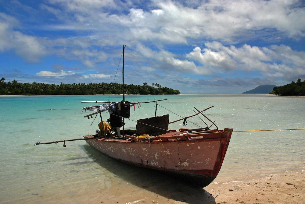 Fishing canoe beached in a sheltered lagoon, Niuatoputapu, Tonga.  The volcanic island of Tafahi can be seen in the distance