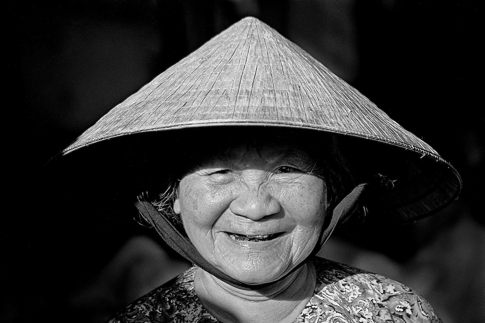 "An elderly Vietnamese woman emerges from the shadows wearing her ""non"" or Vietnamese conical hat."