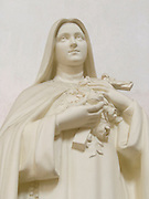 close up of an all white devotional Maria statue with a cross and flowers in her hand