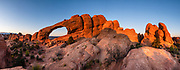 Sunrise light shines on the red-orange sandstone of Skyline Arch at Devils Garden Campground, Arches National Park, Moab, Utah, USA. This image was stitched from multiple overlapping photos. A thick underground salt bed underlies the creation of the park's many arches, spires, balanced rocks, sandstone fins, and eroded monoliths. Some 300 million years ago, a sea flowed into the area and eventually evaporated to create the salt bed up to thousands of feet thick. Over millions of years, the salt bed was covered with debris eroded from the Uncompahgre Uplift to the northeast. During the Early Jurassic (about 210 million years ago) desert conditions deposited the vast Navajo Sandstone. On top of that, about 140 million years ago, the Entrada Sandstone was deposited from stream and windblown sediments. Later, over 5000 feet (1500 m) of younger sediments were deposited and then mostly worn away, leaving the park's arches eroded mostly within the Entrada formation.