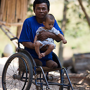 Former Cambodian Government soldier Soeu Sou, 48, looks on from a wheelchair as he holds an unidentified child Saturday, Feb. 14, 2009, near Veal Thom village in Kampon Speu, Cambodia. Sou lost both legs to a landmine while fighting against the Khmer Rouge near Palin, in 1985.  Cambodia continues to wrestle with its past as UN backed tribunals continue for the former leaders of the Khmer Rouge who are accused of genocide.  An estimated 1.5 million Cambodians perished during the reign of the Khmer Rouge.