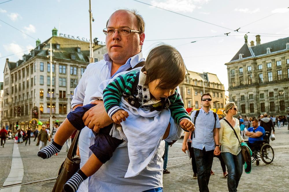 Nederland, Amsterdam, 20-8-2016<br /> Vader draagt klein kind op de Dam.<br />  <br /> Foto: (c) Michiel Wijnbergh