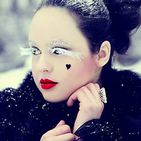 A close-up portrait of a pretty pale girl with black hair, red lips and white feather eyelashes, wearing a black fur coat and standing in the snow.