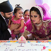 """Hounslow, Greater London, UK, January 25, 2015. Sikh Temple Gurdjwara Sri Guru Singh Sobha. <br /> The Groom and the Bride with Ashreena and their relatives (Sandeep's grandmother in the middle) get together for cutting the cake for the girl's 1st birthday party. """"What made me happy was my little girl's smile when everyone sang Happy Birthday for her"""", says Sandeep, Ashreena's father. <br /> Unlike what usually happens in the Indian community, where even today daughters are not celebrated, Gurmeet and her husband Sandeep decided to give a big party for wishing a happy birthday to their daughter and blessing girls in general."""