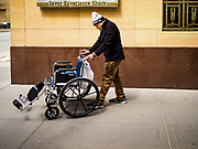 03 MAY 2017 - MINNEAPOLIS, MN: A man pushes his wheelchair up a street in Minneapolis.     PHOTO BY JACK KURTZ