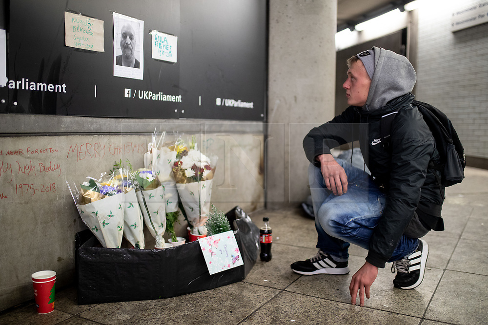 © Licensed to London News Pictures. 20/12/2018. London, UK. Alex Stanley, age 21, places a tribute for his friend Gyula Remes, a Hungarian national found collapsed on 18 December. He died in hospital the following day. According to official statistics published for the first time by the Office for National Statistics, 597 homeless people died in England and Wales in 2017. Photo credit : Tom Nicholson/LNP