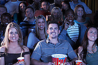 People holding soda and popcorn Watching Movie in Theatre